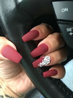 Matte Shade of Red with Flower on Coffin Nails. The matte red with the white clay flowers on is another great way to wear the coffin nails.