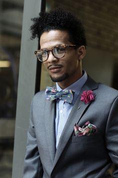 Floral bow tie, grey suit, blue micro gingham shirt, cerise lapel flower, tartan pocket square