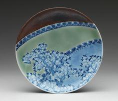 Nabeshima/ Hizen ware dish with cherry blossom design. Edo period, 18th century Japan.   Porcelain with celadon and iron glazes and underglaze blue