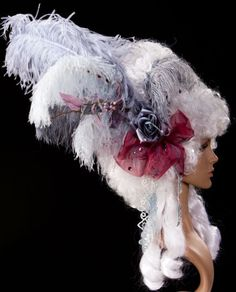 €168,00 EUR. Hair color: white / gray. Ornament color: Variations of grey-blue and violet. Lady's wig extravagantly adorned with feathers, flowers and cords. Artificial hair treated with colored and glittering spray.