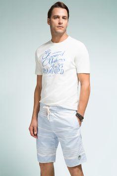 Camiseta branca com estampa localizada em azul, bermuda relax listrada e mix de pulseiras para afirmar o estilo casual.