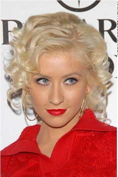 Christina Aguilera has this cute look going for her as her hair is medium length and curly. Her hair has volume to it as it is thick with soft curls styled all around. The look is stylish and perfect for a wedding or prom.The hair is cut to a medium length and in layers.This hair colour is light blonde.