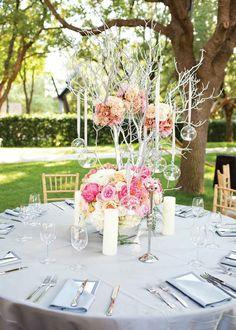 Romantische Tischdekoration mit Arrangement aus weißen Zweigen und Glaskugeln