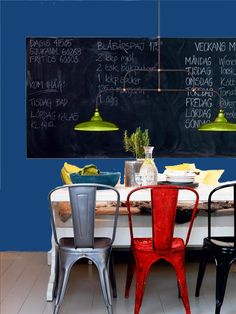 Beautiful bright chairs, a chalkboard wall and bright blue paint-- dynamic combo!