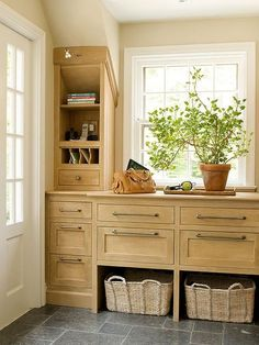 Country mudroom features blond cabinets placed under a window next to a message center alongside a gray slate tiled floor.