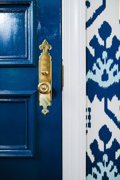 Chic foyer features a glossy blue door adorned with a brass door knob surrounded by walls clad in blue ikat wallpaper, Quadrille Kazak Wallpaper.