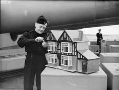Royal Marine J Lynch; Royal Marine J Lynch of Newport building a dolls house, complete with furniture, 1943. In the weeks before Christmas, men and officers in the Royal Navy often put their practical skills to use in making presents for their families at home. This photograph shows Marine Lynch on a battleship putting the finishing touches to a large dolls house, complete with furniture.