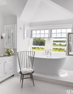 In one of the master baths, the tub is equipped with Waterworks fittings; the aluminum Windsor-style chair is a John Vesey design from the Window.
