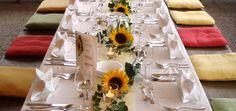 Sonnenblumen --> könnenauch auf den Tisch gelegt werden bzw. Blüten (mit ganz wenig Stiel) in Schalen/Gläsern auf den Tisch, dann kippen sie nicht um. Vielleicht können wir (Du nicht!) relativ kurz vor der Feier die Blumen erst hintun.