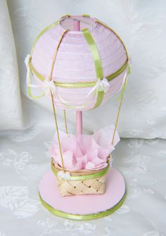 This listing is for (1) hot air balloon in Pink, Light Green and Gold These adorable version of our Hot Air Balloon Centerpieces feature a pink paper lantern and high quality ribbons and embellishments. These beauties would make a unique and beautiful addition to your next event and can be used as a focal point in any childs room or baby nursery. **DESCRIPTIONS** The 6 light pink lantern has been decorated with gold and Ivory ribbons and draping. The little bows are enhanced with a pearl…