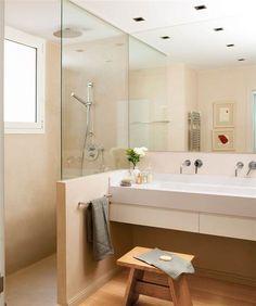 Baño en crema con ducha de obra separado del tocador con un murete rematado con un crtistal transparente a modo de mampara