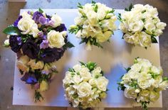 main bouquet with roses, lisianthus, and fressia. white bouquets (for bridesmaids) with roses and fressia.