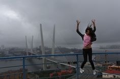 Una mujer salta mientras posa para una foto delante de un cable-apoyado en la ciudad oriental rusa de Vladivostok (Vincent Yu/AP)