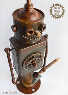 Tin Woodman Sculpture by Robin Davis Studio. This is a One of a Kind Tin Man Sculpture created from a vintage oil can, aged metal tin with rich patina, old clock gears, vintage key and carved axe handle with metal axe head. I use wire to build the fingers and wrap them in thread and
