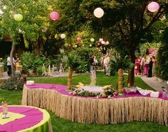 Hawaiian Theme Party Ideas - Really like the straw grass skirt and the pineapple trees on the table.