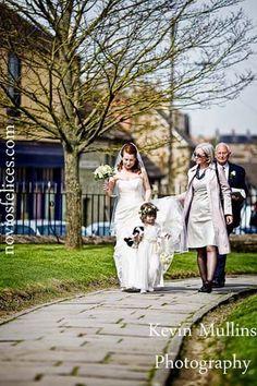 Damita de honor vestida de blanco con ramo tipo bolso y diadema de flores blancas