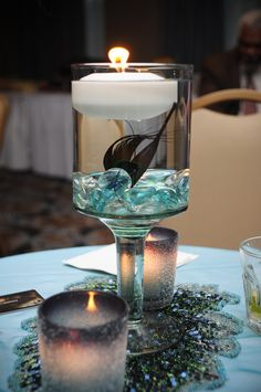 cocktail table centerpiece with floating peacock feather and candle with crystal tealights and placemat