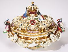 A PAIR OF MEISSEN ARMORIAL RETICULATED TUREENS AND COVERS LAST QUARTER 19TH CENTURY after an eighteenth century model by Johann Joachim Kändler, each double-walled tureen richly gilt on the interior and applied on the exterior with putti and garlands, painted on either side with a topographical panel and affixed on either end with a female bust handle, the cover molded and painted with Kakiemon flowers on the underside and on either side of the coronet knop with the arms of Poland and Saxony