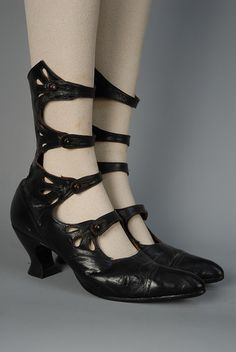 LADY'S HIGH FOUR-STRAP SHOES with CUTWORK, c. 1913 Black kid with cap toe, button straps with three teardrop cutouts at each side. Height 10, heel 2 1/2, length 10 1/2 inches.