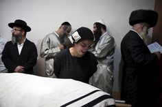 A family member of Aharon Bennett mourns next to his covered body before his funeral in Jerusalem, October 4, 2015. A Palestinian man stabbed and killed two Israelis in Jerusalem's Old City on Saturday before police shot him dead, officers said, amid an uptick in violence in the city and occupied West Bank. REUTERS/Ronen Zvulun