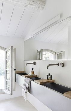 white bathroom walls with trough style sink and large mirror