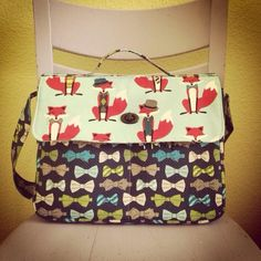 """A classic messenger sewing pattern designed to fit your everyday necessities. Includes options for 3 different flap closures; turn lock, magnetic snaps and side release buckles. Designed to fit a 13"""" laptop perfectly, it includes 4 open pockets and one exterior zippered pocket on the back. Features both a long adjustable strap and a top handle for those grab-and-go moments."""