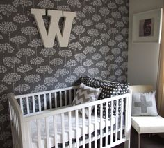 This gray and white wallpaper is the focal point of this modern vintage nursery!