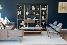 Blue mid-century modern living room features deep blue walls positioned behind a wood and brass 3 piece styled shelving unit that faces a marble top mid-century modern coffee table flanked by a taupe sofa with a chaise lounge and two side by side blue mid-century modern chairs placed on a white wool rug.