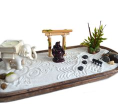 This zen garden sits upon a wooden oval base and features a variety of items to create your own perfect centerpiece! The miniature laughing Buddha statue is a symbol of happiness and contentment. The elephant statue comes with a scented candle for you to