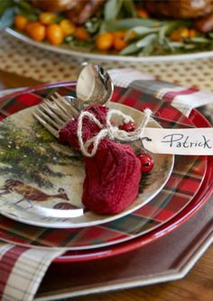 Silverware tucked into tiny stockings as a cute place setting idea for Christmas dinner.