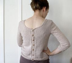 This cardigan is knitted with a buttoning back, which can be opened. The cardigan is wearable with both the buttons in front and on the back, since the cardigan is shaped similar on both sides.
