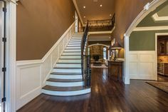Traditional Staircase with High ceiling, Crown molding, Wainscoting, Hardwood floors