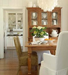Cozy Cottage, Bold Accents, Inviting Dining Room:   When the homeowner looked at the rooms of this house, she didn't let their intended purpose determine how her family would live. She transformed the living room into a dining room that accommodates her large dining table and many guests. Around the table, mismatched chairs continue the home's casual atmosphere. A hutch made from recycled barn wood is the focal point of the room and shows off her dishware.  Get the Look: Have fun in a room…