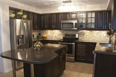 ... Classy Small Kitchen Design with Espresso Wood Kitchen Cabinets and Island and Dark Grey Granite Countertops ...