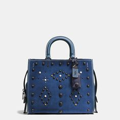 Pearl cabochons and polished gunmetal rivets—each one applied by hand—update our exceptionally well crafted Rogue bag with a striking cowboy punk look that is still quite refined. Inspired by the free-spirited Coach girl, this silhouette is crafted in rich suede with contrast stitching and metal feet on the bottom to protect the leather.