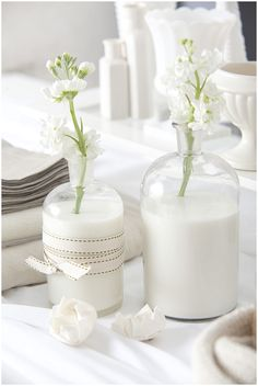 Beautiful idea for an all white table...... use milk instead of water for the vases!