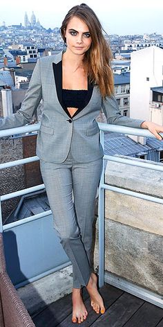 """Last Night's Look: Love It or Leave It?   CARA DELEVINGNE    taking a break (sorta) from Paris Fashion Week to toast YSL's """"The Luxurious Mascara"""" in a sharp gray suit, bandeau bra, and, yep, no shoes."""