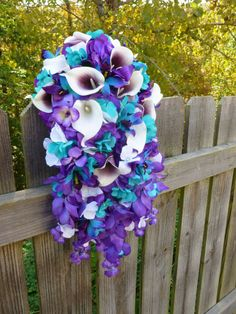 This beautiful bouquet is made with purple fabric hydrangeas, wisterias, handpainted purple blue orchids and real touch Picasso and white calla lilies. Turquoise hydrangeas are close to Davids bridal Malibu color. Bouquets handle is wrapped with your choice of satin ribbon and has