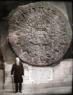 Porfirio Díaz standing next to the Aztec Sun Stone.