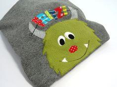 """Diese Mütze ist in einem schönen Melangegrau gearbeitet. Auch ein kleines Monster hat sich auf der Mütze einen Platz gesucht. Jede """"triste"""" Jacke w..."""