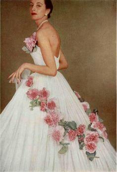 1951 Dior- Merveilleuse robe de tulle agrémentée de rosés trémières fleurissant entièrement la jupe.