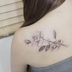 Delicate blackwork rose tattoo on back shoulder by Tattooist Flower