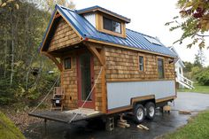 The Acorn House by Nelson Tiny Houses. A charming and cozy tiny house with a unique cedar shingle exterior.