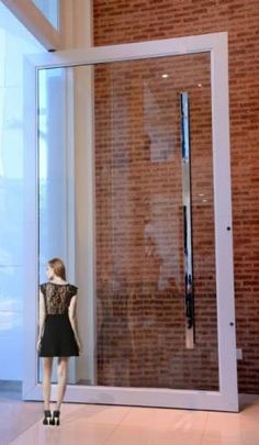 Porta Pivotante: vidro, moldura branca e puxador grande.
