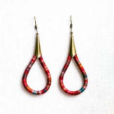 Red Ombre Earrings - cotton thread wrapped . a pair of drop shaped earrings wrapped in vibrant hand dyed thread in the warm tones of red with a surprising pop of blue . materials. hand dyed cotton thread brass (nickel free) measures. 5,7 x 2,3 cm would you like it in another color? i would be happy to create a special color palette for you! (no added costs) thanks for visiting! Enjoy :) (these earrings are handmade by me, original and ready to ship in a pretty packag...