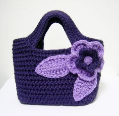 Violet handbag. I wonder if I could replicate this. It looks like a project in the round with a flat bottom, similar to starting a shoe. Then when you get to the handles, you just chain a bunch and start crocheting further down the line when you get a good handle length. Follow that for a few more rows, and voila, a handbag.