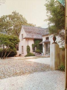 Hamptons aged stucco, cedar roof, metal canopy, pea gravel