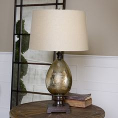 Uttermost Boulangerie Lamp. Antiqued mercury glass with distressed script and aged mango wood details. The round, slightly tapered hardback shade is a taupe beige linen fabric.