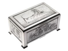 Silver cigarette box commemorating Battleship HMS 'King George V' - given to George V by his mother. It is rectangular with feet at corners and hinged lid. 4 sides are decorated relief panels: HMS 'King George V' super dreadnought; ships of Armada in action; Blake's ship 'St George' off Santa Cruz; Tudor Royal Standard at time of Armada; contemporary Royal Standard.