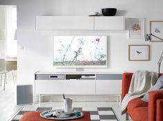 Biały pokój dzienny z białym zestawem do przechowywania mediów i TV UPPLEVA oraz pomarańczową sofą NOCKEBY
